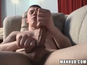 Cute looking guy jerks his cock on a couch